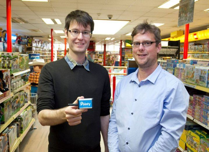 Two men stand in a shop holding a Pointy device.