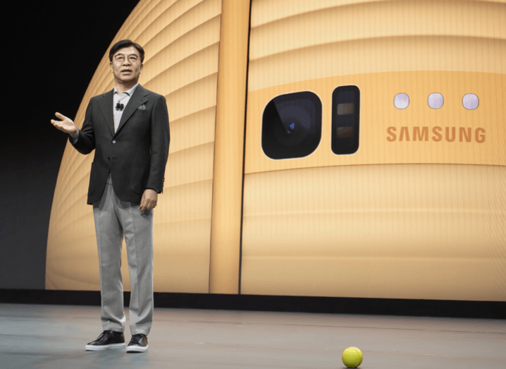 A man wearing a black suit jacket, grey trousers and black trainers stands on stage presenting a yellow ball to the audience at CES.