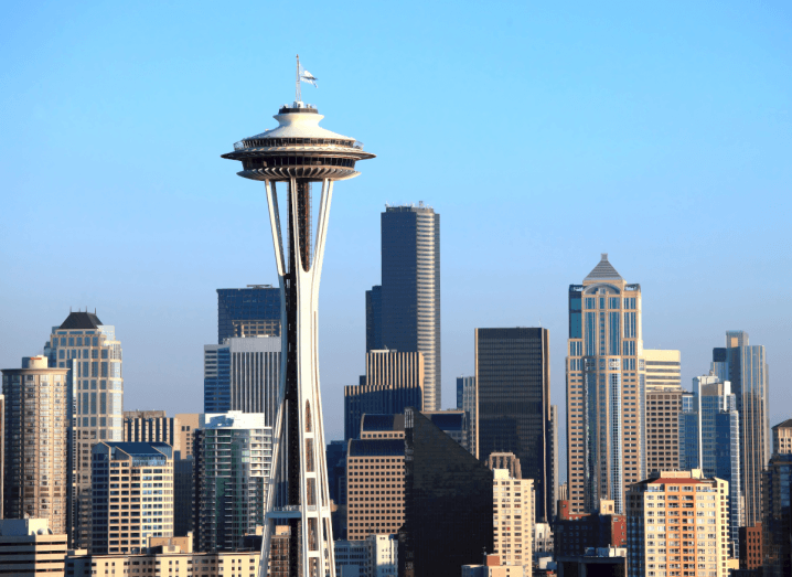 The skyline of Seattle, featuring recognisable structures in front of a blue sky.
