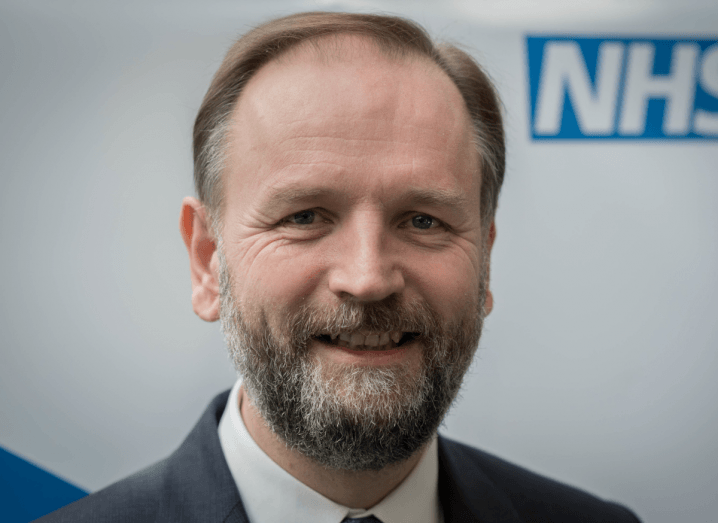 A man with a grey beard and light brown hair wearing a grey suit stands in front of a white wall with the NHS logo on it. He is smiling at the camera.