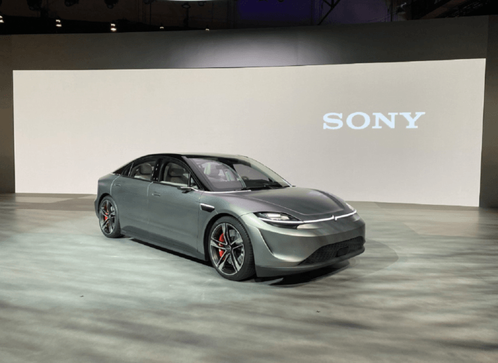 A sleek, grey vehicle with a black roof, on display in front of the Sony logo.