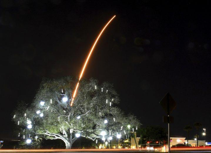 A tree by a roadside is lit up against a dark sky, and a bright red trail of the Falcon 9 rocket is seen emerging from behind it, rising into the stratosphere.