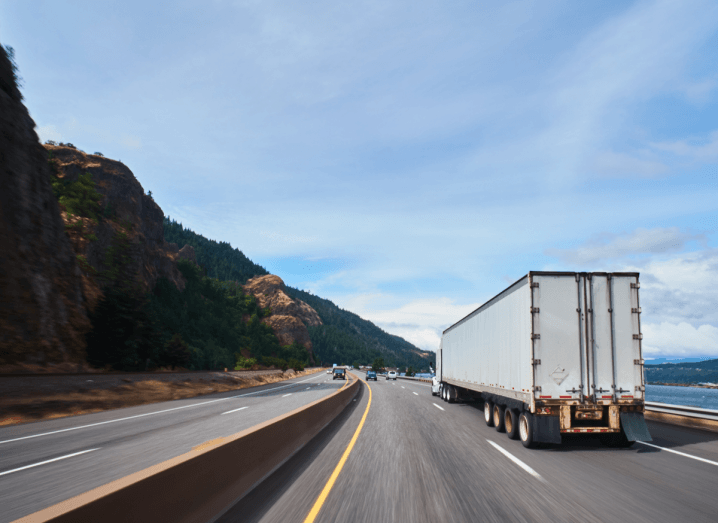 The rear end of a truck travelling on a motorway beside a mountain and a lake.