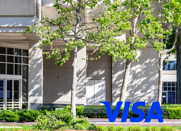 The blue Visa logo on the ground outside an office building, beside trees and bushes.