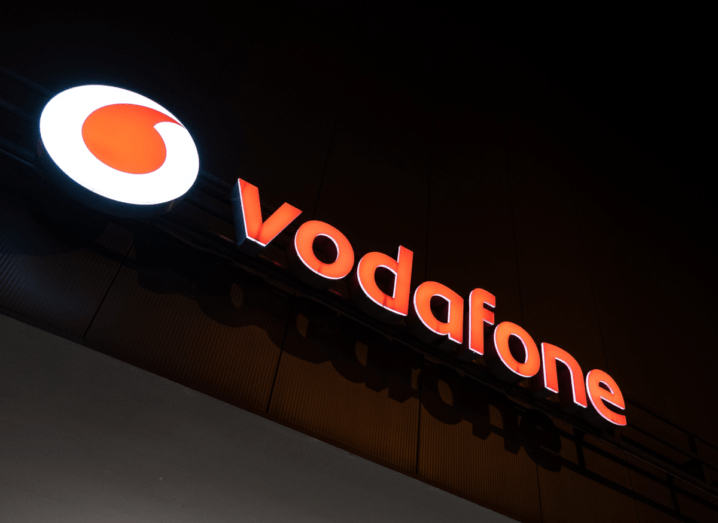 The Vodafone logo lit up in the dark on the front of a shop.