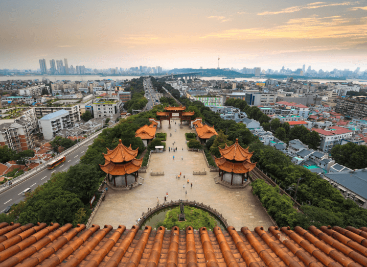 A rooftop view of traditional Chinese buildings surrounded by a modern sprawling city.