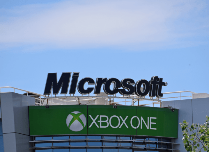 The Microsoft logo above a sign that says Xbox One on top of a building. There is a blue sky above it with some wispy white clouds.