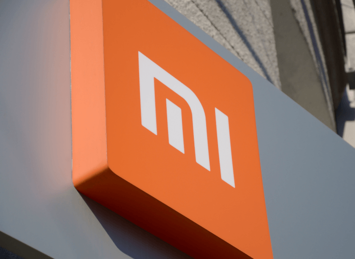 An orange Xiaomi logo on the front of a grey store.