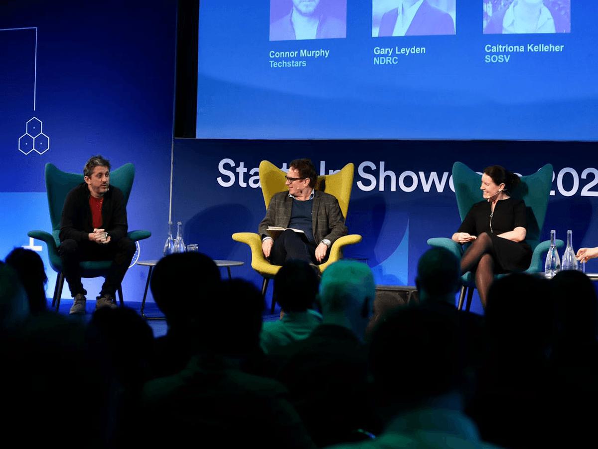 Three people sitting on armchairs on stage.