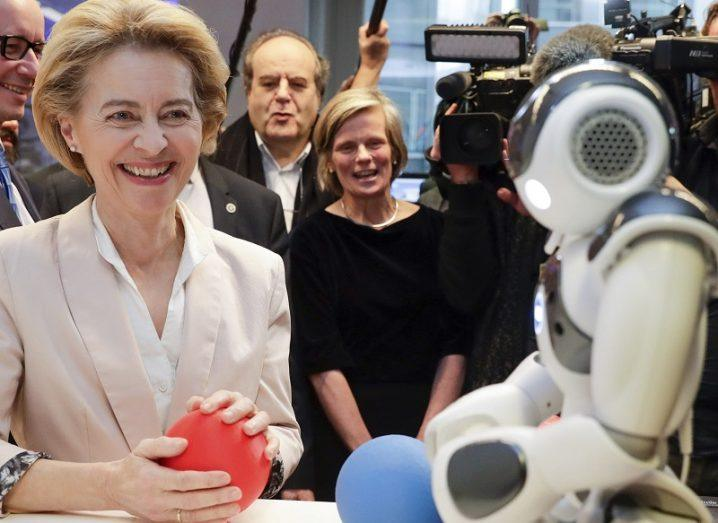 Ursula von der Leyen smiling in a white blazer while holding a red ball and playing with a robot with a blue ball.