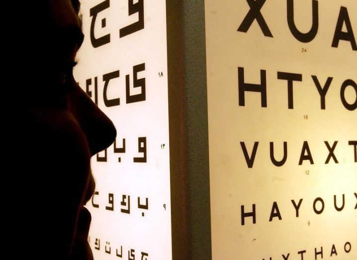 Silhouette of a person looking at an eye test chart with large letters.
