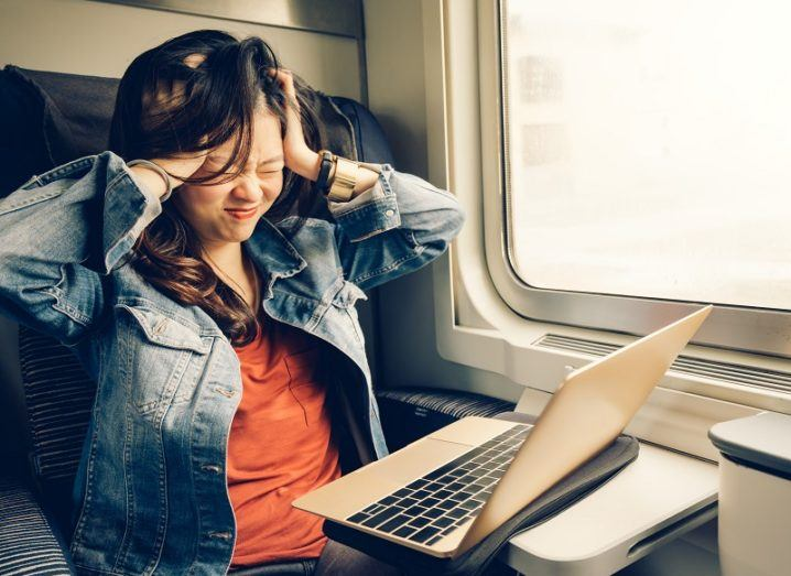 Woman in a denim jacket and orange t-shirt holding her head in her hands in frustration, while using a laptop on a train.