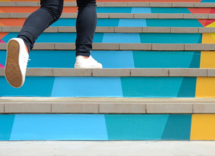 The legs of a person wearing jeans and white sneakers, running up a colourful set of stairs.