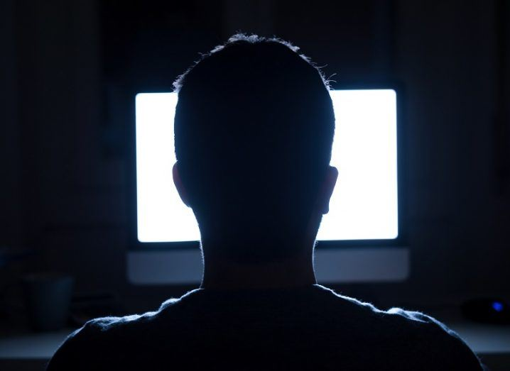 Silhouette of man's head in front of computer monitor light in a dark room.
