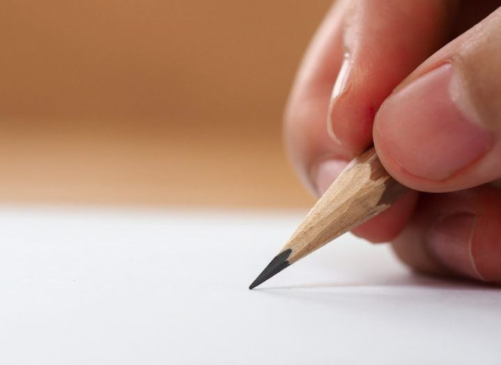 Close-up of fingers gripping a pencil with the tip touching a page.