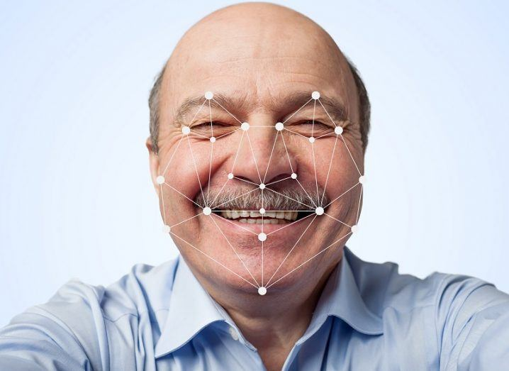 Elderly man with a moustache smiling with facial recognition points rendered over his face against a white background.