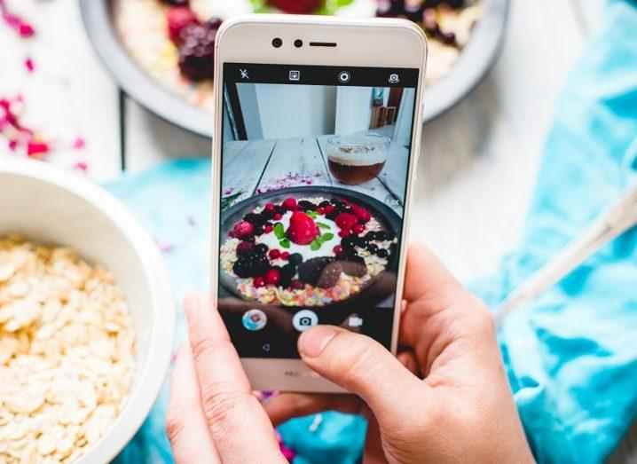 Person holding their phone and taking a photo of a fruity pancake on a wooden table covered with a blue cloth.