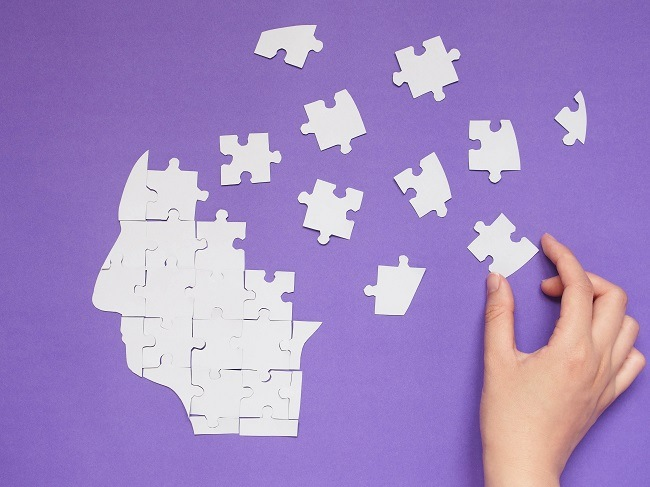 A hand putting together a head-shaped jigsaw puzzle against a purple background.