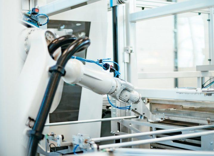 A white robotic arm in a research facility working on a production line.