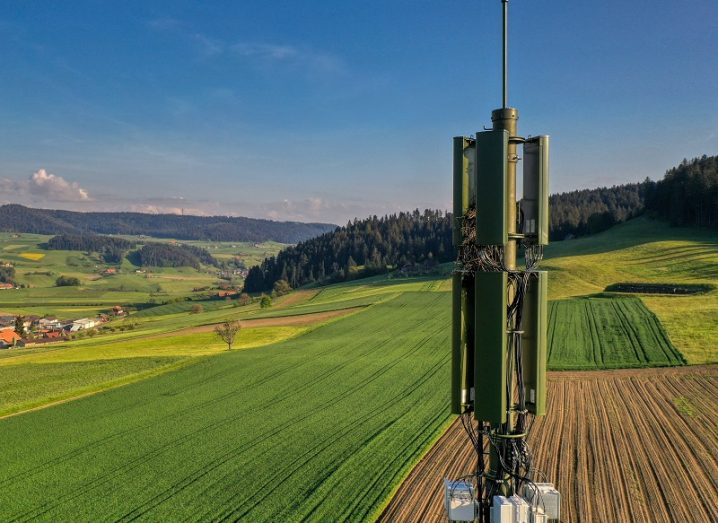 Green 5G mast in the foreground with rolling, Swiss fields in the background and a blue sky.