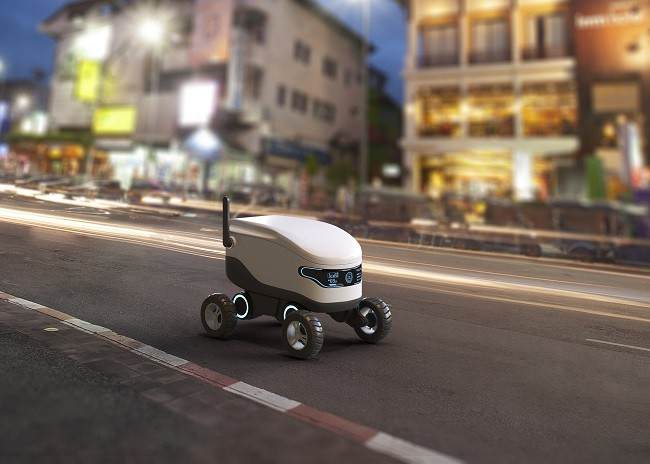An autonomous delivery robot driving down an empty road on a city street.