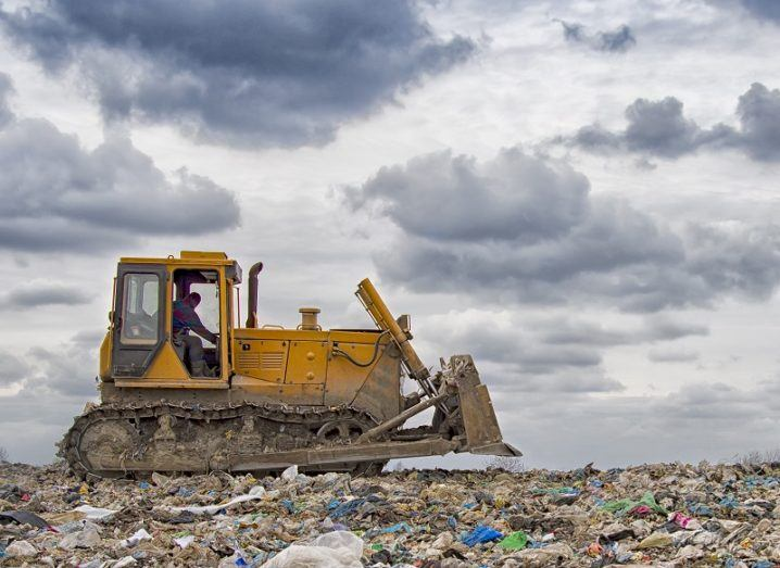 Ground shot of a bulldozer driving across a field of plastic waste against a grey sky background.