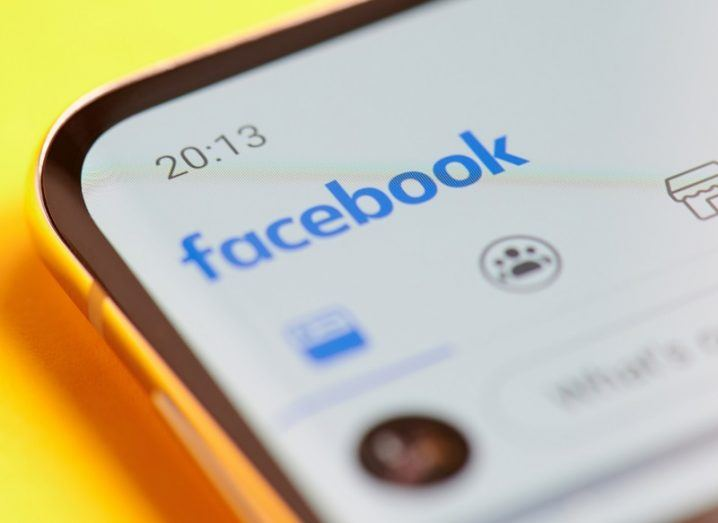 Close-up of the Facebook app on a phone against a yellow background.