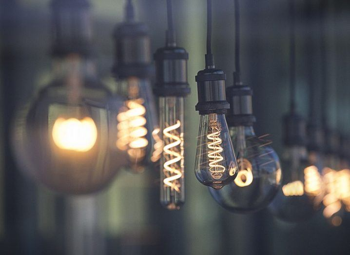 A row of lightbulbs, each a different shape and size, are lit and hanging from a ceiling.