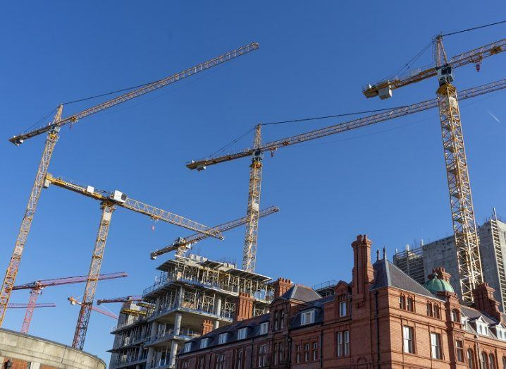 Many cranes towering over buildings in Dublin against a blue sky.