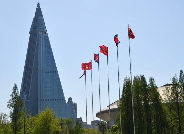The towering, pyramid-shaped Ryugyong Hotel in Pyongyang with North Korean flags in the foreground.