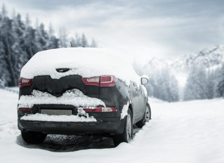 A black car covered in snow, parked in a snowy landscape scene, with trees in the background.