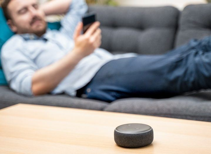 Man lying on the couch looking at his phone while an Amazon Echo Dot sits on the table.