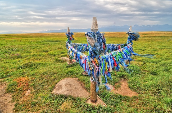 A Buryat shaman site with totems and bull stone in a triangle shape against a vast plains background.