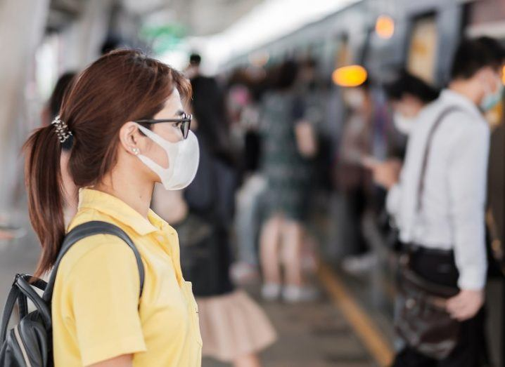 Young woman wearing a medical face mask, standing on a train platform.