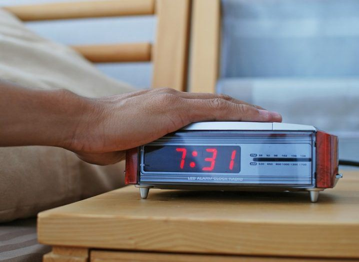 Hand on top of a digital alarm clock on a wooden side table.