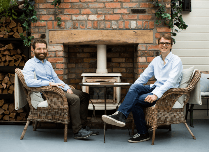 Two men in light blue shirts sit on wicker chairs in front of a stone fireplace.