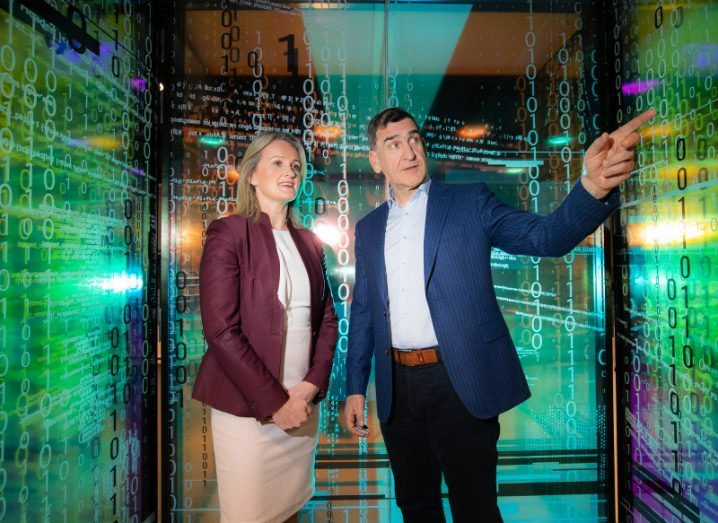 A man and a woman stand in a glass-panelled cubicle with binary code and other text covering the walls. The man points to something out of picture and the woman looks on.