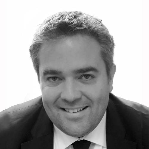 Black and white image of David Kindlon smiling into the camera.