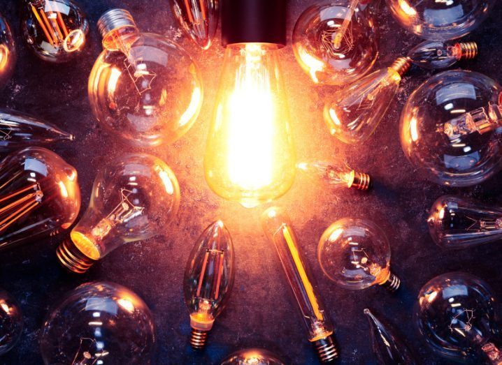 Light bulb glowing yellow on rough dark background surrounded by burnt out bulbs, representing digital transformation.
