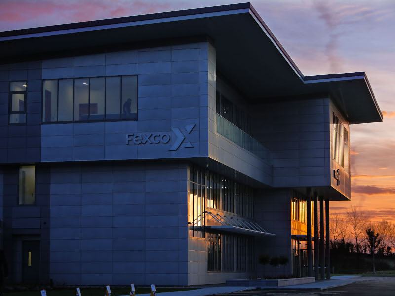 A large grey Fexco building, photographed at sunset.