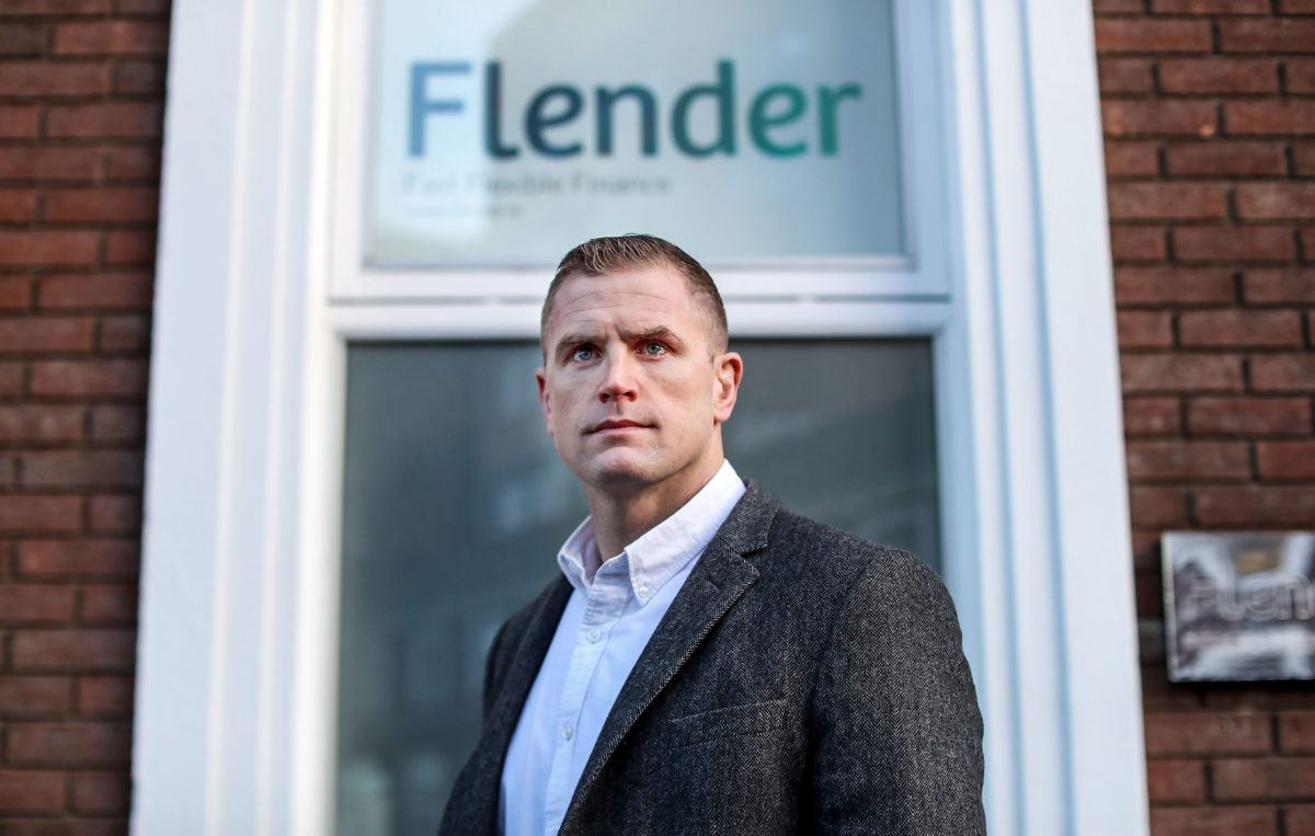 A man in a grey suit stands outside of a red brick building in front of the Flender logo.