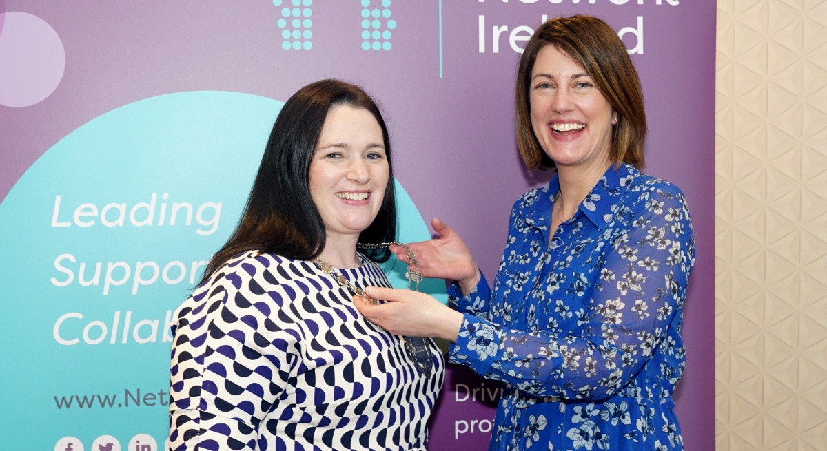 Two women are standing together in front of a Network Ireland banner, smiling into the camera.