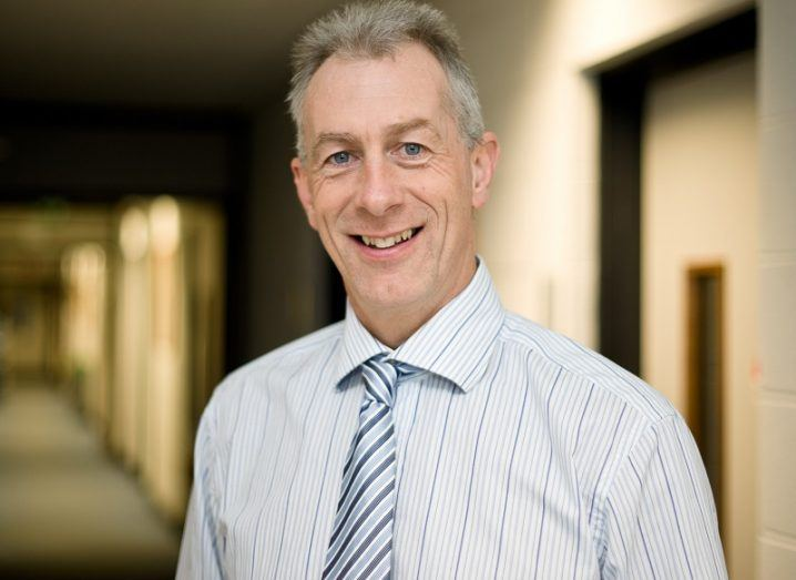 Prof John Ringwood smiling in a white shirt and blue and pink tie, standing in a hallway.