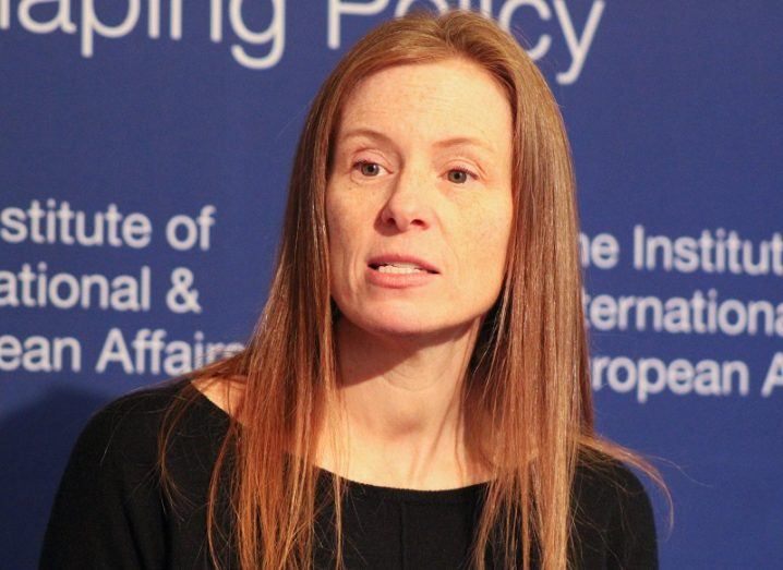 Headshot of Monika Bickert in a black top, pictured against a blue background with white text.