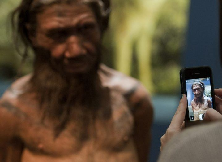Wax model of a Neanderthal man with a person taking a photo of him using a phone.