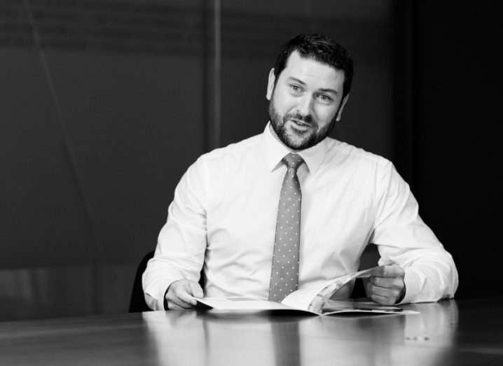 A black and white photo of a man in a shirt and tie, sitting at a boardroom table with a book. He is Niall Corrigan from EY.