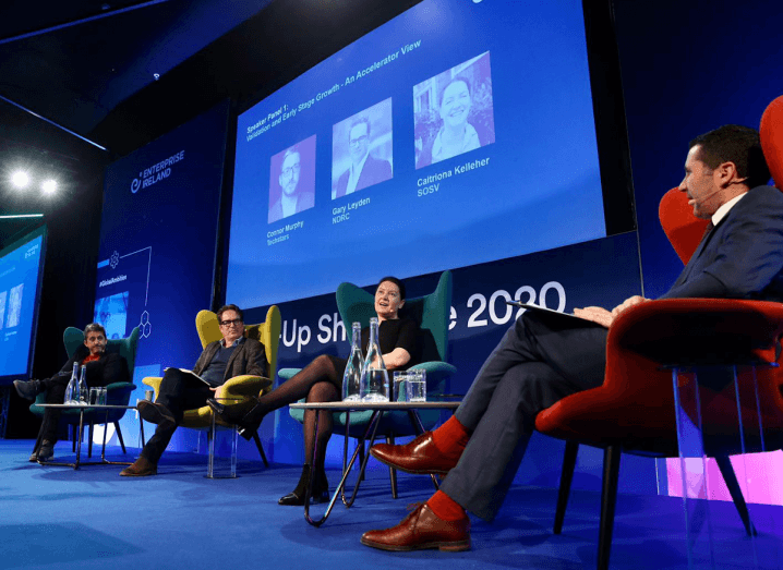 A group of people sit on armchairs on a stage in front of photographs of themselves. The man furthest to the left is Connor Murphy of Techstars who is wearing dark clothes and black shoes. To the right of him is Gary Leyden from NDRC who is wearing a brown sports jacket, navy jumper and black trousers. To the right of Leyden is Caitriona Kelleher who is wearing a black dress. Finally, furthest to the right is a man moderating the panel, who is wearing a navy suit with red socks and brown shoes.