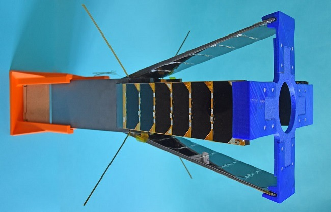 A long cubesat with fins to increase drag during re-orbit and a square orange top on one end and a blue cross on the other.