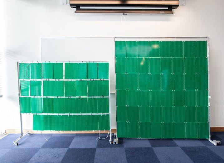 The smart surface material coloured green hanging up in front of a white wall and on a blue checkered floor.