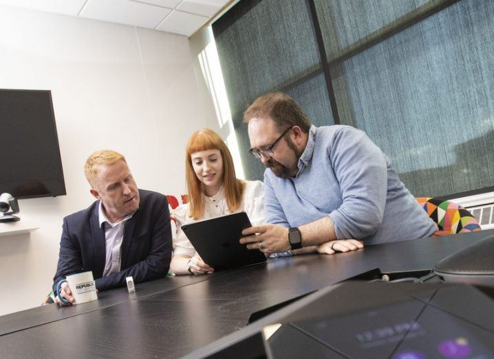 Three people huddle over a tablet device in a meeting room.